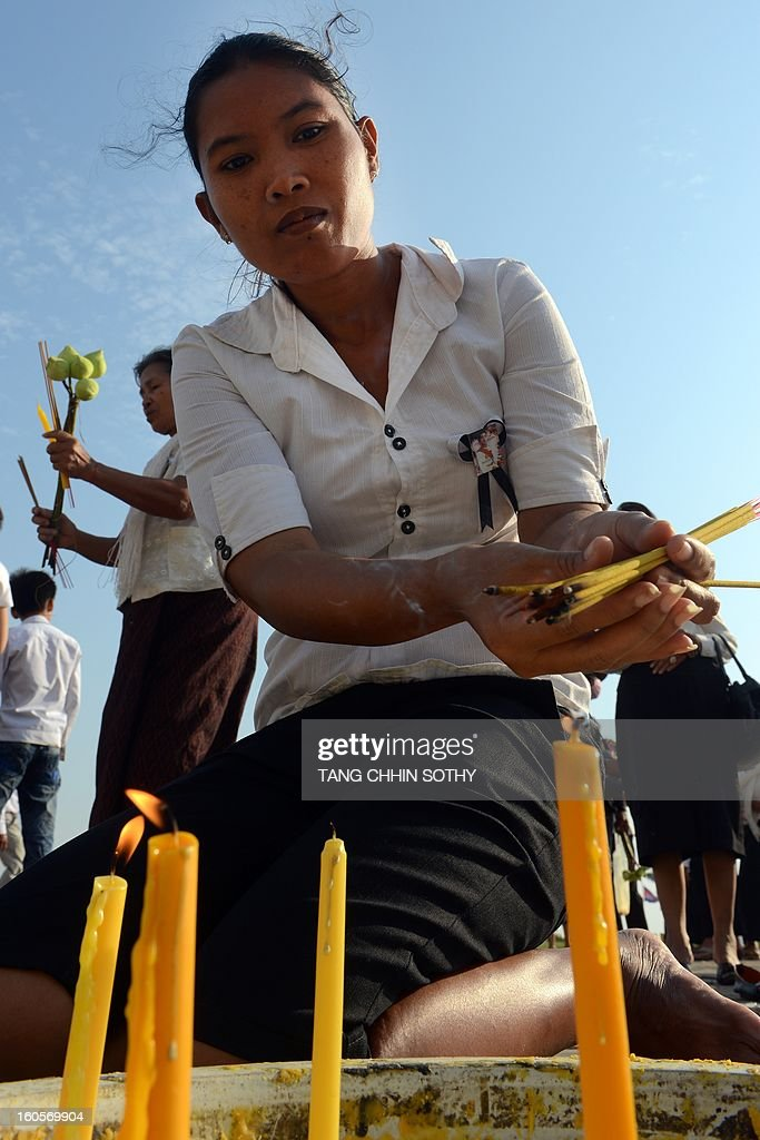 A Cambodian woman lights incense sticks as she pays her respects to the late former king Norodom Sihanouk in front of the Royal Palace in Phnom Penh on February 3, 2013. Thousands of Cambodians have paid their last respects to their beloved former king Norodom Sihanouk as his body lay in state ahead of his cremation on February 4.