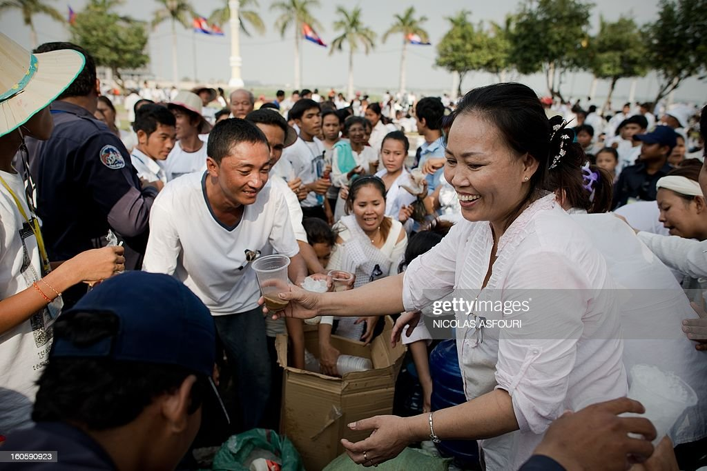 A Cambodian woman offers free coffee to people who come to pray and pay their respects for the late former king Norodom Sihanouk near the Royal Palace in Phnom Penh on February 3, 2013. Thousands of Cambodians have paid their last respects to their beloved former king Norodom Sihanouk as his body lay in state ahead of his cremation on February 4. AFP PHOTO/ Nicolas ASFOURI