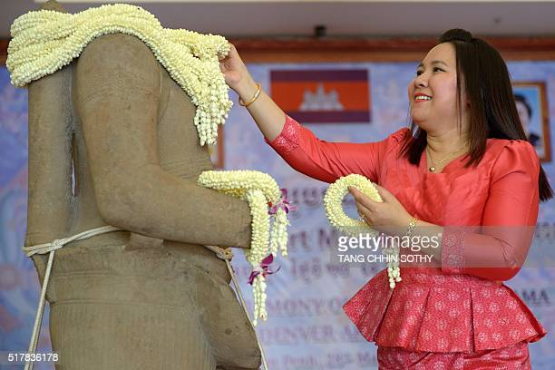 A Cambodian woman places a garland around a 10thcentury sandstone sculpture of the Hindu god Rama after it was returned from the Denver Art Museum in...