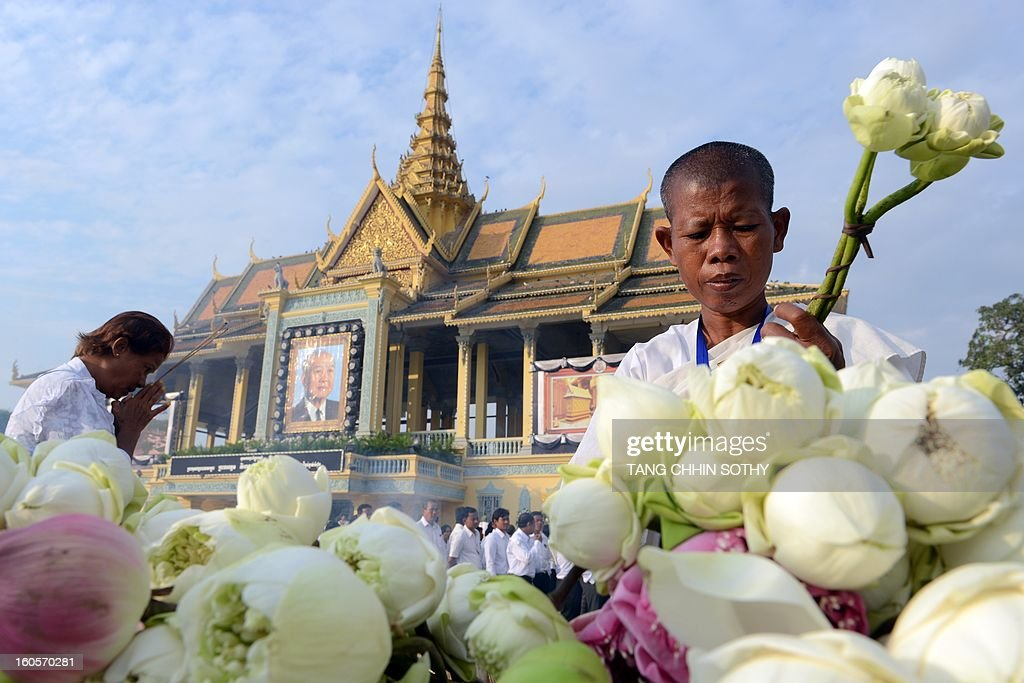 A Cambodian woman (L) prays as another (R) holds flowers as people pay their respects to the late former king Norodom Sihanouk in front of the Royal Palace in Phnom Penh on February 3, 2013. Thousands of Cambodians have paid their last respects to their beloved former king Norodom Sihanouk as his body lay in state ahead of his cremation on February 4.