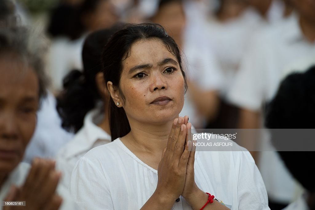 A Cambodian woman prays as she queues to enter the crematorium area where the coffin of Cambodia's late king Norodom Sihanouk rests before his cremation near the Royal Palace in Phnom Penh on February 4, 2013. Cambodia was due to hold an elaborate cremation ceremony for its revered former king Norodom Sihanouk, part of a week-long funeral for the colourful late royal. AFP PHOTO / Nicolas ASFOURI