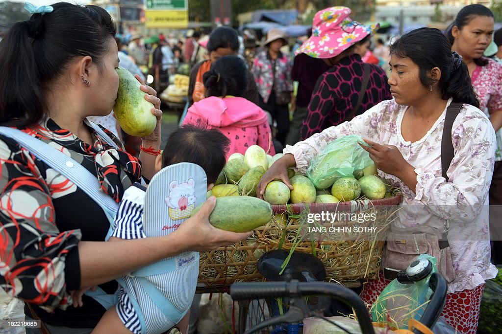 A Cambodian woman (L) selects fresh produce at a market in Phnom Penh on February 21, 2013. Cambodia's economic growth accelerated to 7.3 percent last year thanks to buoyant activity in the agricultural, tourism, construction and garment sectors, Prime Minister Hun Sen said on February 20, 2013. AFP PHOTO / TANG CHHIN SOTHY