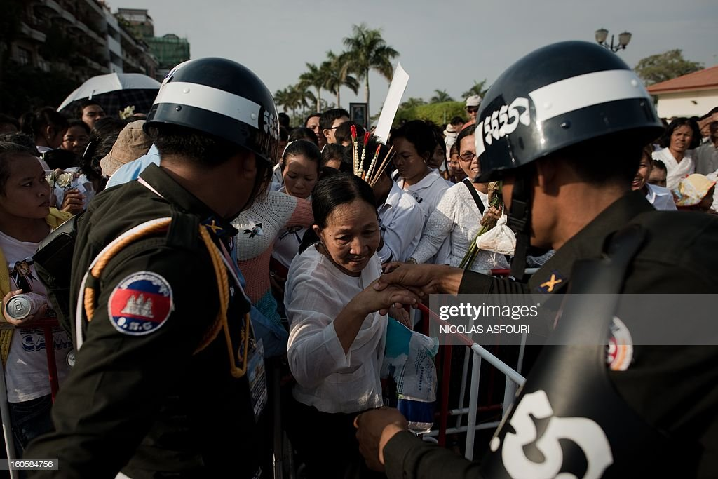 A Cambodian woman (C) tries to make her way through barriers, helped by police officers as people come to pray and pay their respect for the late former king Norodom Sihanouk near the Royal Palace in Phnom Penh on February 3, 2013. Thousands of Cambodians have paid their last respects to their beloved former king Norodom Sihanouk as his body lay in state ahead of his cremation on February 4. AFP PHOTO/ Nicolas ASFOURI