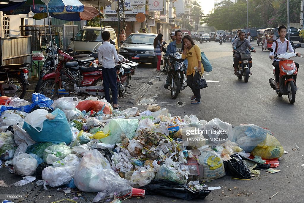 A Cambodian woman walks near a rubbish pile along a street ...