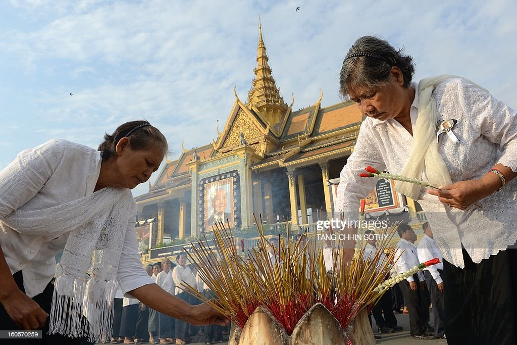 Cambodian women use incense sticks as they pay their respects to late former king Norodom Sihanouk in front of the Royal Palace in Phnom Penh on February 3, 2013. Thousands of Cambodians have paid their last respects to their beloved former king Norodom Sihanouk as his body lay in state ahead of his cremation on February 4. AFP PHOTO / TANG CHHIN SOTHY