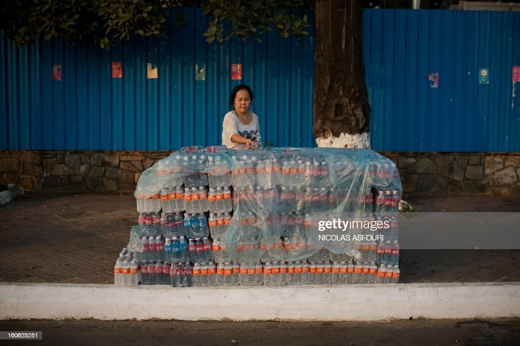A Cambodian worker displays free bottles of water to hand out to mourners near the crematorium area where the body of Cambodia's late king Norodom Sihanouk rests before his cremation near the Royal Palace in Phnom Penh on February 4, 2013. Cambodia was due to hold an elaborate cremation ceremony for its revered former king Norodom Sihanouk, part of a week-long funeral for the colourful late royal. AFP PHOTO / Nicolas ASFOURI