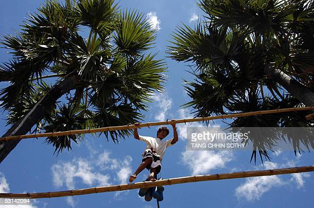 Cambodian worker moves from one tree to another to collect sugar palm juice for Palm Beer on the outskirts of the capital city Phnom Penh 20 June...