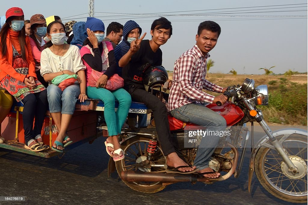 A Cambodian worker (C) shows a victory sign as he sit with other workers on motor-cart vehicle travelling along the national road number 5 in Kampong Chhnang province, some 90 kilometers north of Phnom Penh on March 22, 2013. Cambodia has raised the minimum wage for its garment workers by 20 percent, following a series of strikes over pay and conditions, but union leaders said Friday it was not enough. AFP PHOTO/ TANG CHHIN SOTHY
