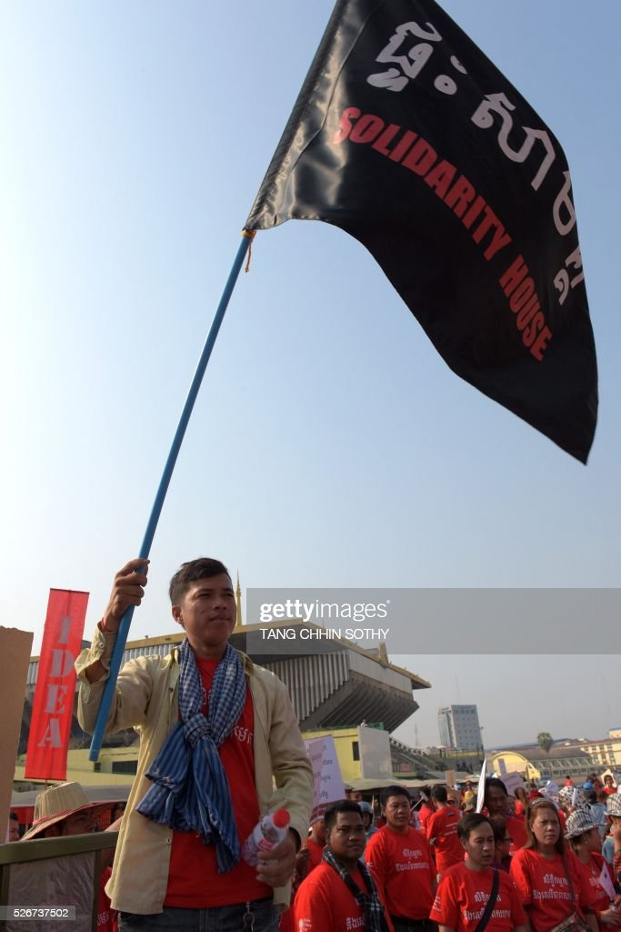 A Cambodian worker waves a flag to mark May Day, or International Workers Day, in Phnom Penh on May 1, 2016. Activists around the world mark May Day with marches demanding better working conditions, more jobs and higher wages. / AFP / TANG