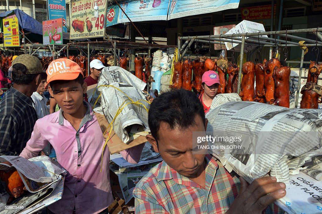 Cambodian workers carry roast pigs at a market ahead of the Lunar New Year in Phnom Penh on February 7, 2016. While not a holiday in Cambodia, the Lunar New Year, the most important holiday in China and a number of countries in east and southeast Asia, starts on February 8 bringing in the 'Year of the Monkey'. AFP PHOTO / TANG CHHIN SOTHY / AFP / TANG CHHIN SOTHY