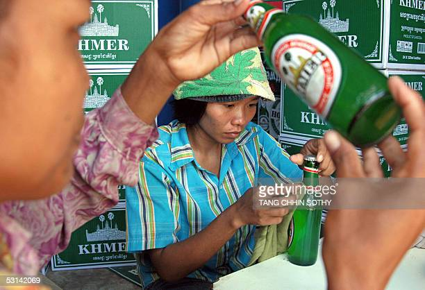 Cambodian workers check logos of the Palm Beer at a factory in Phnom Penh 20 June 2005 In a humble hut built from the leaves of Cambodia's famed...