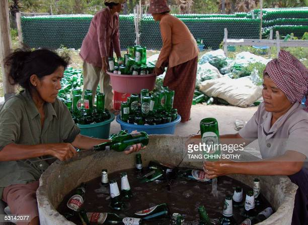 Cambodian workers clean beer bottles for refilling with sugar palm beer at a makeshift smallscale factory site on the outskirts of the capital city...