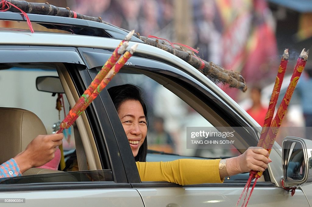 Cambodian-Chinese hold incense sticks through the windows of a car after visiting a temple to mark the start of the Lunar New Year in Kandal province on February 8, 2016. While not a holiday in Cambodia, the Lunar New Year, the most important holiday in China and a number of countries in east and southeast Asia, started on February 8 bringing in the 'Year of the Monkey'. AFP PHOTO / TANG CHHIN SOTHY / AFP / TANG CHHIN SOTHY