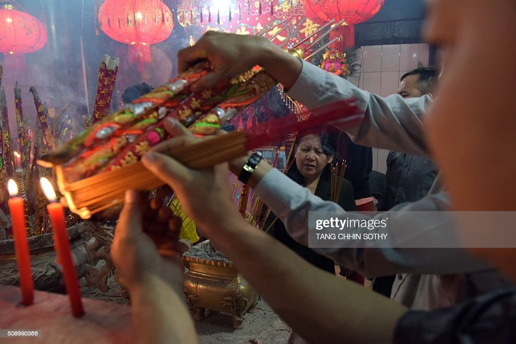 Cambodian-Chinese light incense sticks and pray at a temple to mark the start of the Lunar New Year in Kandal province on February 8, 2016. While not a holiday in Cambodia, the Lunar New Year, the most important holiday in China and a number of countries in east and southeast Asia, started on February 8 bringing in the 'Year of the Monkey'. AFP PHOTO / TANG CHHIN SOTHY / AFP / TANG CHHIN SOTHY