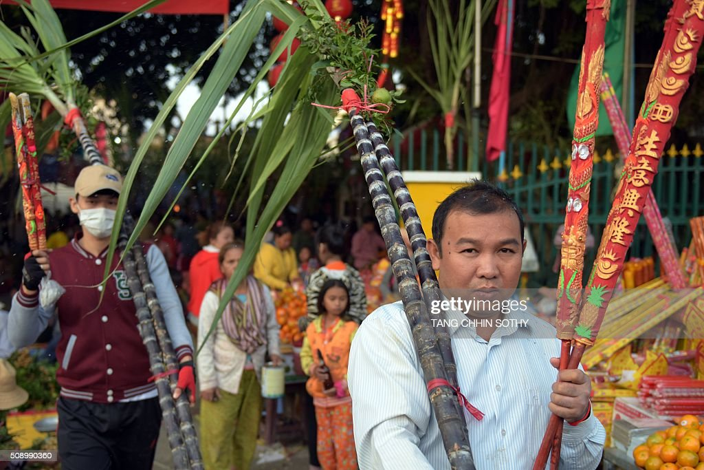 Cambodian-Chinese men carry incense sticks (R) and sugar cane (C) from a temple as people visit to mark the start of the Lunar New Year in Kandal province on February 8, 2016. While not a holiday in Cambodia, the Lunar New Year, the most important holiday in China and a number of countries in east and southeast Asia, started on February 8 bringing in the 'Year of the Monkey'. AFP PHOTO / TANG CHHIN SOTHY / AFP / TANG CHHIN SOTHY