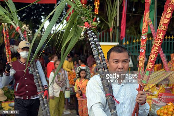 CambodianChinese men carry incense sticks and sugar cane from a temple as people visit to mark the start of the Lunar New Year in Kandal province on...