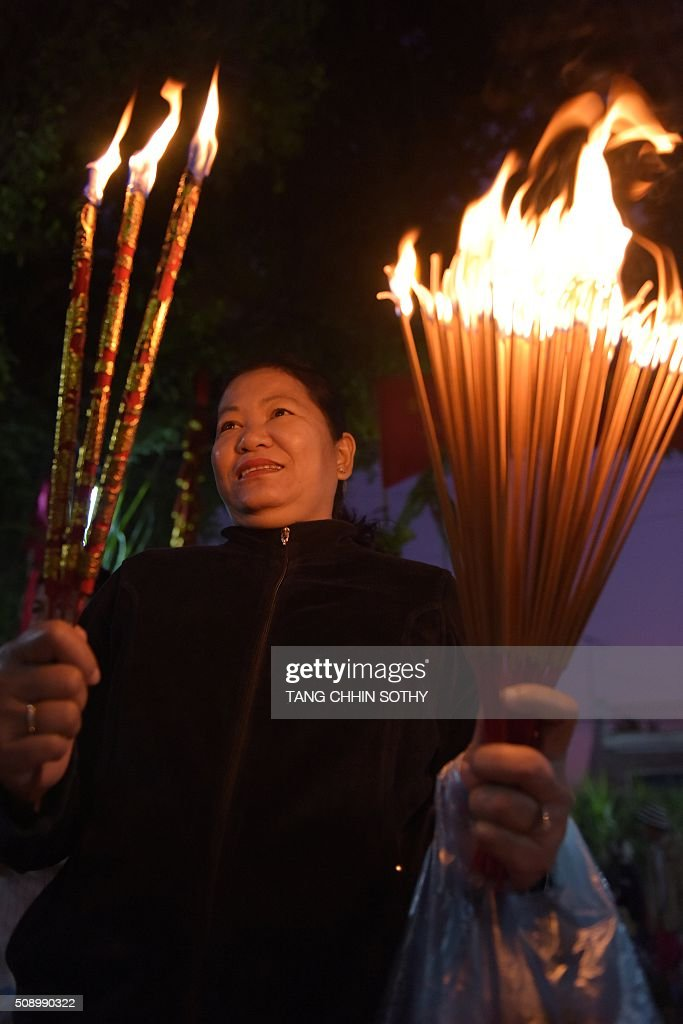 A Cambodian-Chinese woman burns incense sticks at a temple to mark the start of the Lunar New Year in Kandal province on February 8, 2016. While not a holiday in Cambodia, the Lunar New Year, the most important holiday in China and a number of countries in east and southeast Asia, started on February 8 bringing in the 'Year of the Monkey'. AFP PHOTO / TANG CHHIN SOTHY / AFP / TANG CHHIN SOTHY