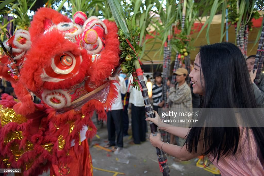 A Cambodian-Chinese woman smiles as she holds sugar cane in front of a lion dance at a temple as people mark the start of the Lunar New Year in Kandal province on February 8, 2016. While not a holiday in Cambodia, the Lunar New Year, the most important holiday in China and a number of countries in east and southeast Asia, started on February 8 bringing in the 'Year of the Monkey'. AFP PHOTO / TANG CHHIN SOTHY / AFP / TANG CHHIN SOTHY