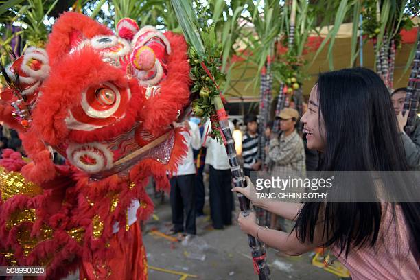 A CambodianChinese woman smiles as she holds sugar cane in front of a lion dance at a temple as people mark the start of the Lunar New Year in Kandal...