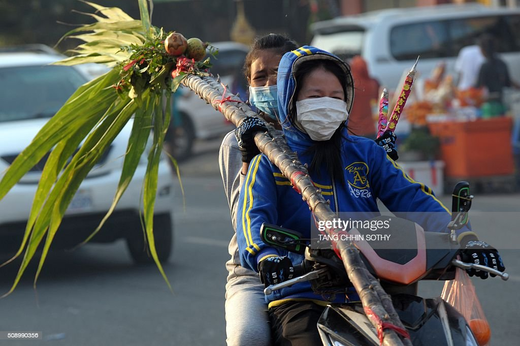 Cambodian-Chinese women carry incense sticks and sugar cane on their motorbike after visiting a temple to mark the start of the Lunar New Year in Kandal province on February 8, 2016. While not a holiday in Cambodia, the Lunar New Year, the most important holiday in China and a number of countries in east and southeast Asia, started on February 8 bringing in the 'Year of the Monkey'. AFP PHOTO / TANG CHHIN SOTHY / AFP / TANG CHHIN SOTHY