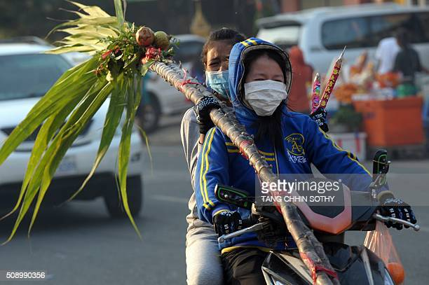 CambodianChinese women carry incense sticks and sugar cane on their motorbike after visiting a temple to mark the start of the Lunar New Year in...