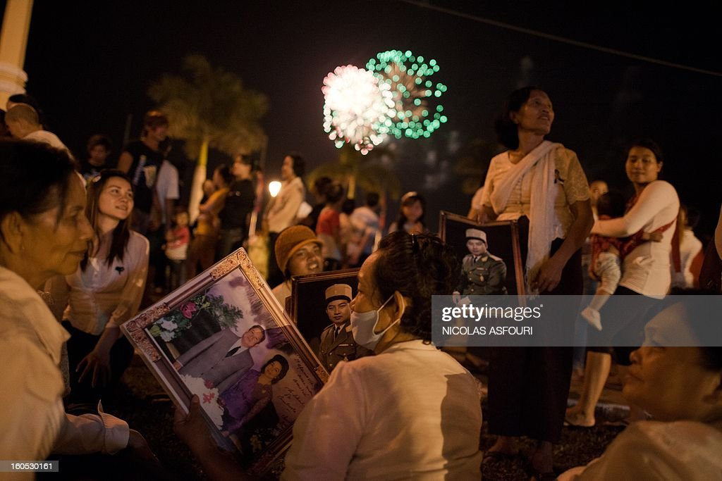 Cambodians buy photographs of Cambodia's late King Norodom Sihanouk in front of the Royal Palace as fireworks light up the sky in Phnom Penh on February 2, 2013. A sea of mourners filled the streets of the Cambodian capital on February 1, for a lavish funeral for revered former king Norodom Sihanouk, who towered over six tumultuous decades in his nation's history. AFP PHOTO/ Nicolas ASFOURI