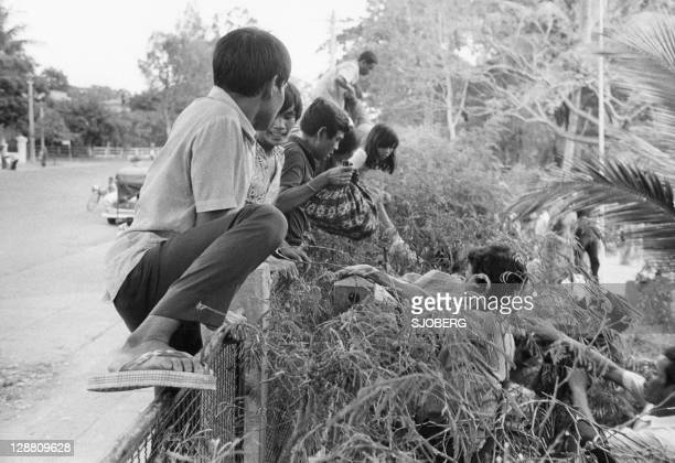 Cambodians fearing the Khmer Rouges climb the fence surrounding the French Embassy in Phnom Penh late April 1975 On New Year's Day 1975 Communist...