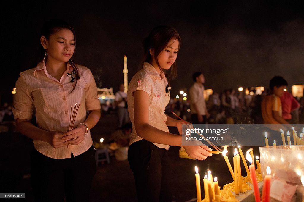 Cambodians light candles and incense as they pay their respects to the late former king Norodom Sihanouk infront of the Royal Palace in Phnom Penh on February 3, 2013. Thousands of Cambodians have paid their last respects to their beloved former king Norodom Sihanouk as his body lay in state ahead of his cremation on February 4. AFP PHOTO/ Nicolas ASFOURI