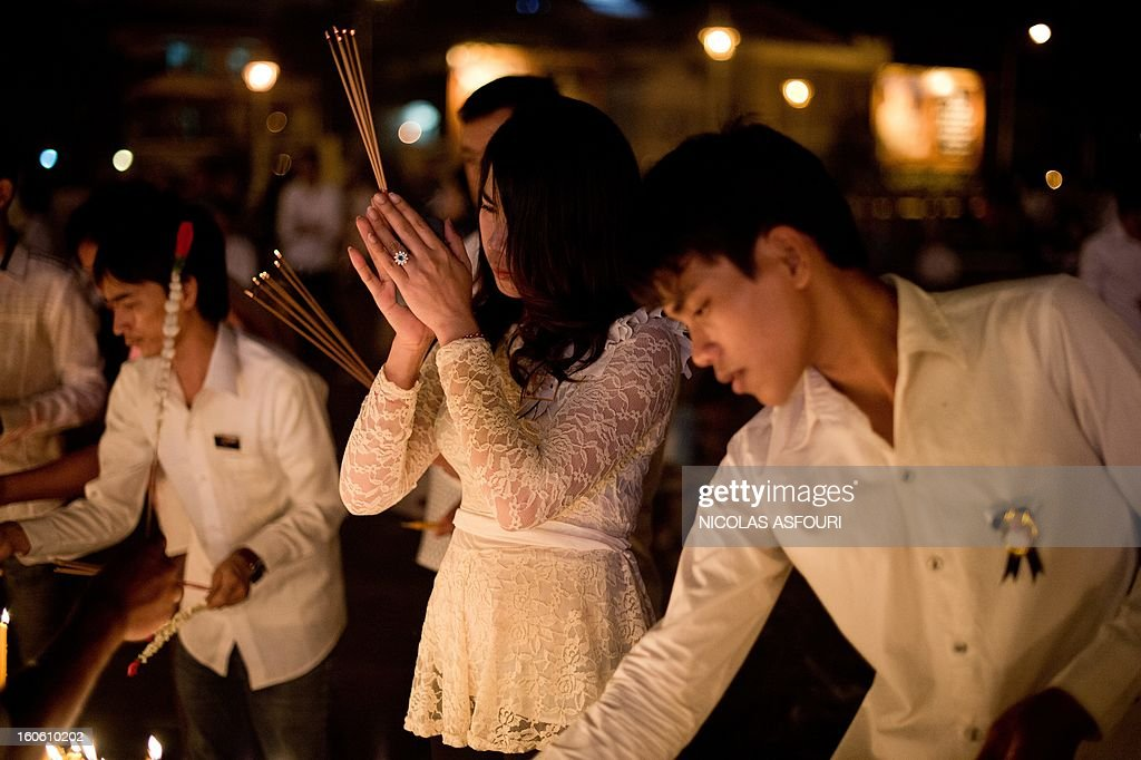 Cambodians light candles and incense as they pay their respects to the late former king Norodom Sihanouk infront of the Royal Palace in Phnom Penh on February 3, 2013.Thousands of Cambodians have paid their last respects to their beloved former king Norodom Sihanouk as his body lay in state ahead of his cremation on February 4. AFP PHOTO/ Nicolas ASFOURI