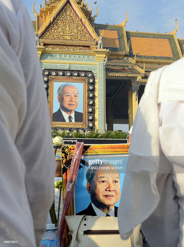 Cambodians pay their respects in front of portraits of the late former king Norodom Sihanouk in front of the Royal Palace in Phnom Penh on February 3, 2013. Thousands of Cambodians have paid their last respects to their beloved former king Norodom Sihanouk as his body lay in state ahead of his cremation on February 4.