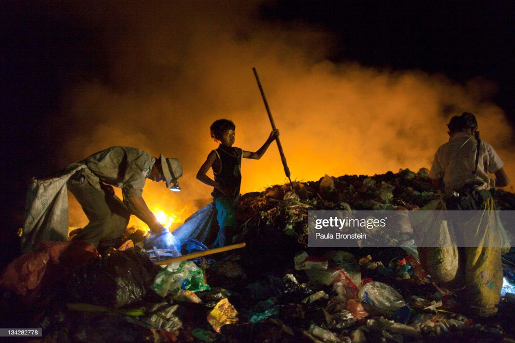Cambodians work late into the night recycling garbage as fires burn at the local garbage dump November 30, 2011 in Siem Reap, Cambodia. Many children work part time in the dump to help support their families while attending school during the day. While Siem Reap's ancient temples boost massive tourism attracting millions of visitors still 28.3% of Cambodians live on less than $1.25 per day according to a 2011 UNDP Human Development Report. An estimated 36 per cent of Cambodia's 14.2 million people live below the poverty line and about 85 per cent of these live in rural areas.