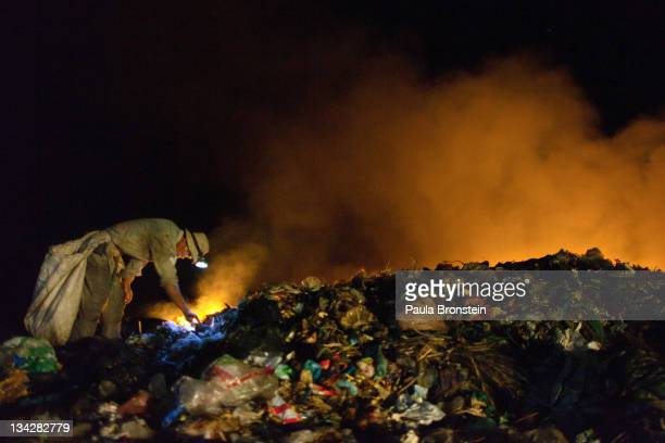 Cambodians work late into the night recycling garbage as fires burn at the local garbage dump November 29 2011 in Siem Reap Cambodia Many children...
