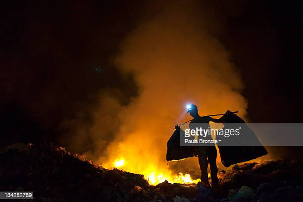 Cambodians work late into the night recycling garbage as fires burn at the local garbage dump November 30 2011 in Siem Reap Cambodia Many children...
