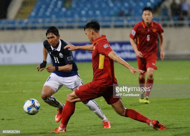 Cambodia's Chan Vathanaka fights for the ball with Vietnam's Doan Van Hau during the AFC Asian 2019 Cup qualifier at Hanoi's My Dinh stadium on...