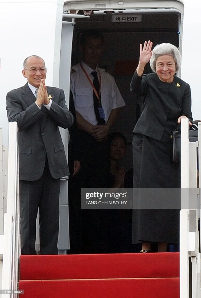 Cambodia's King Norodom Sihamoni (L) and his mother, former queen Monique (R), wave to wellwishers before departing to Beijing for medical check-ups at Phnom Penh International Airport on August 12, 2013.