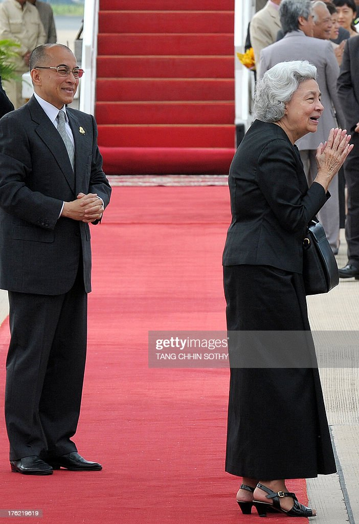 Cambodia's King Norodom Sihamoni (L) and his mother, former queen Monique (R), greet people before departing to Beijing for medical check-ups at Phnom Penh International Airport on August 12, 2013.
