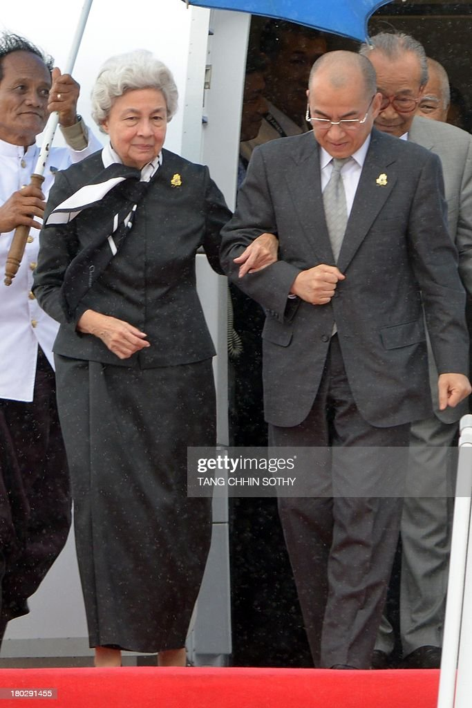 Cambodia's King Norodom Sihamoni (R) and his mother, former queen Monique (L), walk down from a plane upon their arrival at Phnom Penh International Airport on September 11, 2013. Cambodian King Norodom Sihamoni returned from Beijing where he underwent medical check-ups. AFP PHOTO/ TANG CHHIN SOTHY