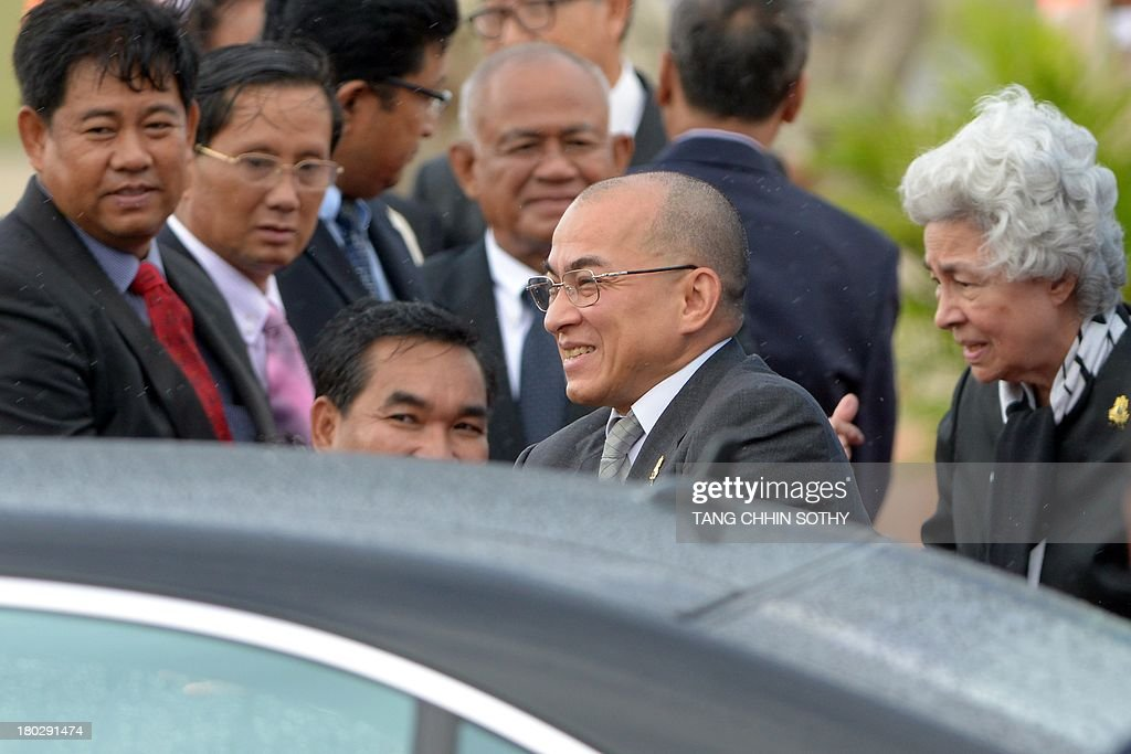Cambodia's King Norodom Sihamoni (C) and his mother, former queen Monique (R), greet government officials upon their arrival at Phnom Penh International Airport on September 11, 2013. Cambodian King Norodom Sihamoni returned from Beijing where he underwent medical check-ups.