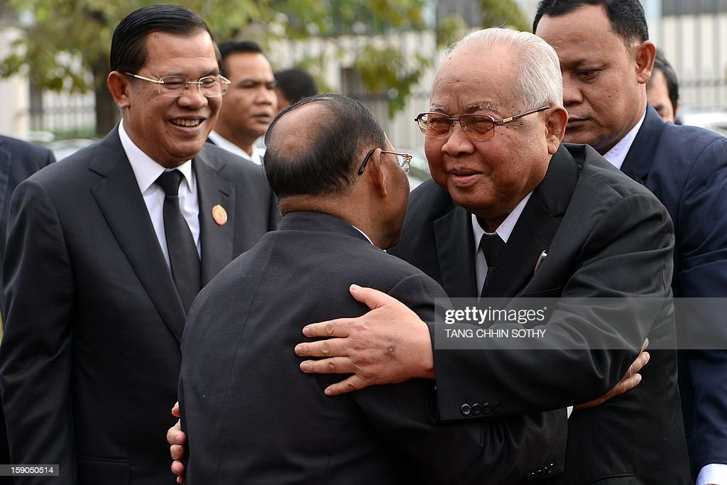Cambodia's president of the senate and president of the Cambodian People's Party (CPP) Chea Sim (R) embraces president of the National Assembly and vice president of Cambodian People's Party (CPP) Heng Samrin (C) upon his arrival as Prime Minister Hun Sen (L) smiles during a CPP ceremony marking the 34th anniversary of the fall of the Khmer Rouge regime at CPP headquarters in Phnom Penh on January 7, 2013. Some Cambodians criticise the January 7 anniversary, saying it represents the start of a decade-long occupation by Vietnam rather than a day of liberation while Hun Sen, a former Khmer Rouge cadre before he fled to Vietnam in 1977 and joined the resistance, has been Cambodia's prime minister since 1985.