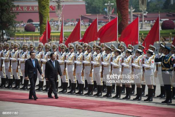 Cambodia's Prime Minister Hun Sen reviews a military honour guard with Chinese Premier Li Keqiang during a welcome ceremony outside the Great Hall of...