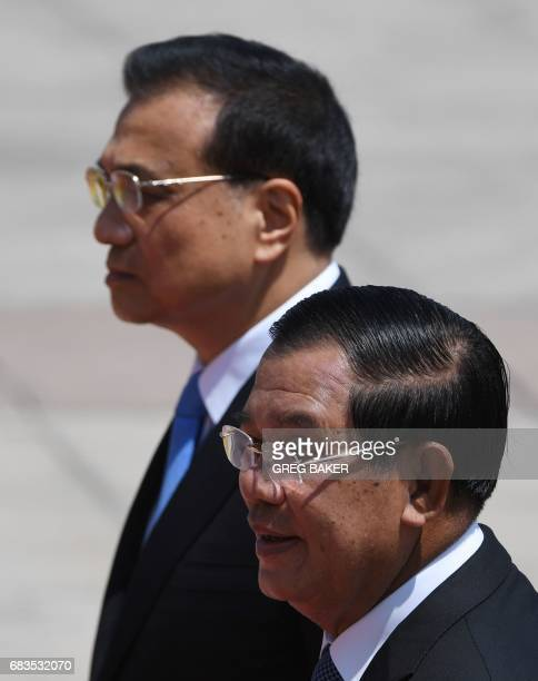 Cambodia's Prime Minister Hun Sen walks with Chinese Premier Li Keqiang during a welcome ceremony outside the Great Hall of the People in Beijing on...