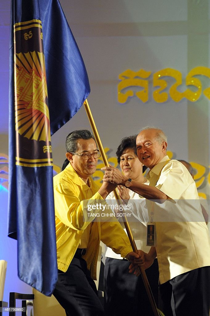 Cambodia's Prince Norodom Ranariddh (R), son of the late monarch <a gi-track='captionPersonalityLinkClicked' href=/galleries/search?phrase=Norodom+Sihanouk&family=editorial&specificpeople=210861 ng-click='$event.stopPropagation()'>Norodom Sihanouk</a> and half-brother of the current king Norodom Sihamoni, receives a party's flag during the Royalist FUNCINPEC party congress in Phnom Penh on January 19, 2015. Cambodian Prince Norodom Ranariddh was officially named the head of the royalist party on January 19, seen as a tactic by the country's strongman leader Hun Sen to divide the opposition.