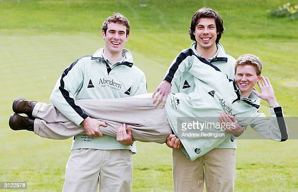 Cambridge crew members Hugo Mallinson and Steffen Buschbacher hold up cox Kenelm Richardson during the WeighIn and Photo call on March 23 2004 at The...