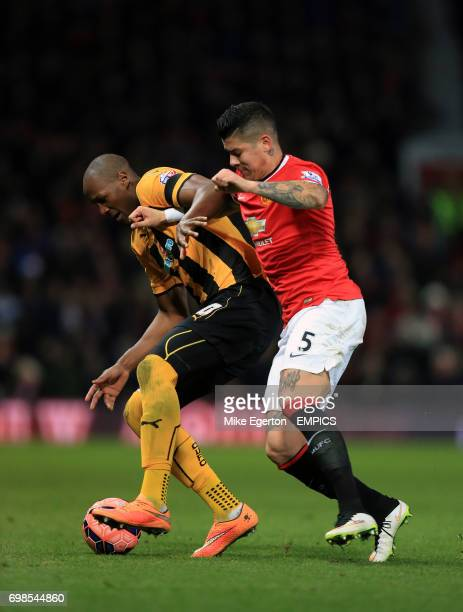Cambridge United's Tom Elliott and Manchester United's Marcos Rojo battle for the ball
