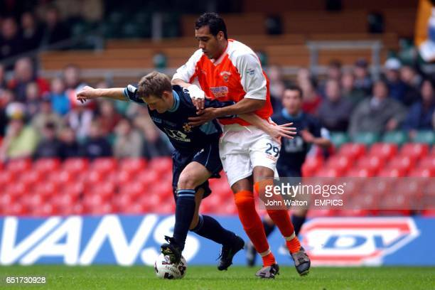Cambridge United's Tom Youngs battles for possession of the ball with Blackpool's goalscorer Chris Clarke