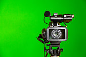 Camcorder on a green background. Filming in the interior. The chroma key.
