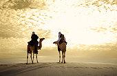 Camel riders in desert during sunset