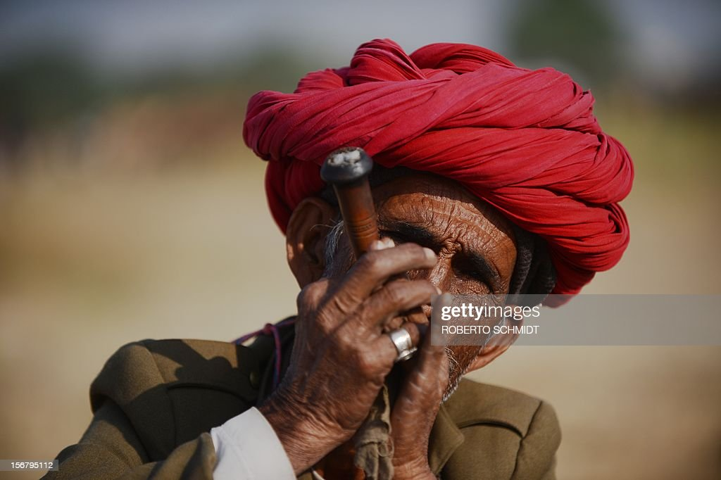 A camel trader smokes a pipe at the camel fair grounds in the outskirts of the small town of Pushkar on November 20, 2012. The annual five-day camel and livestock fair, held in the town of Pushkar in the state of Rajasthan is one of the world's largest camel fairs, and apart from buying and selling of livestock it has become an important tourist attraction. AFP PHOTO/Roberto Schmidt