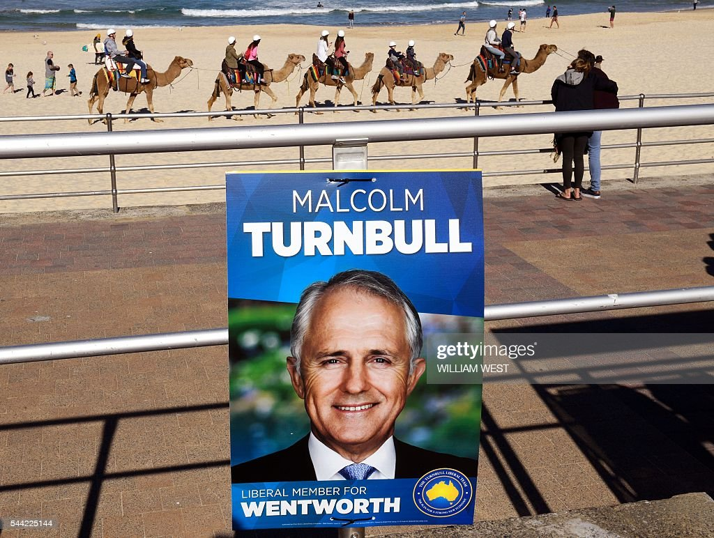 Camels carry tourist past an election placard outside a voting station in the Sydney suburb of Bondi Beach on July 2, 2016. Australians flocked to vote in the national election with conservative leader Malcolm Turnbull appearing to have a slight edge over Labor's Bill Shorten, culminating a marathon race where economic management has become a key issue in the wake of the Brexit vote. / AFP / WILLIAM