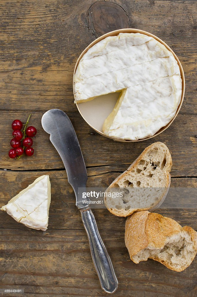 Camember cheese with red currant and baguette on wooden table